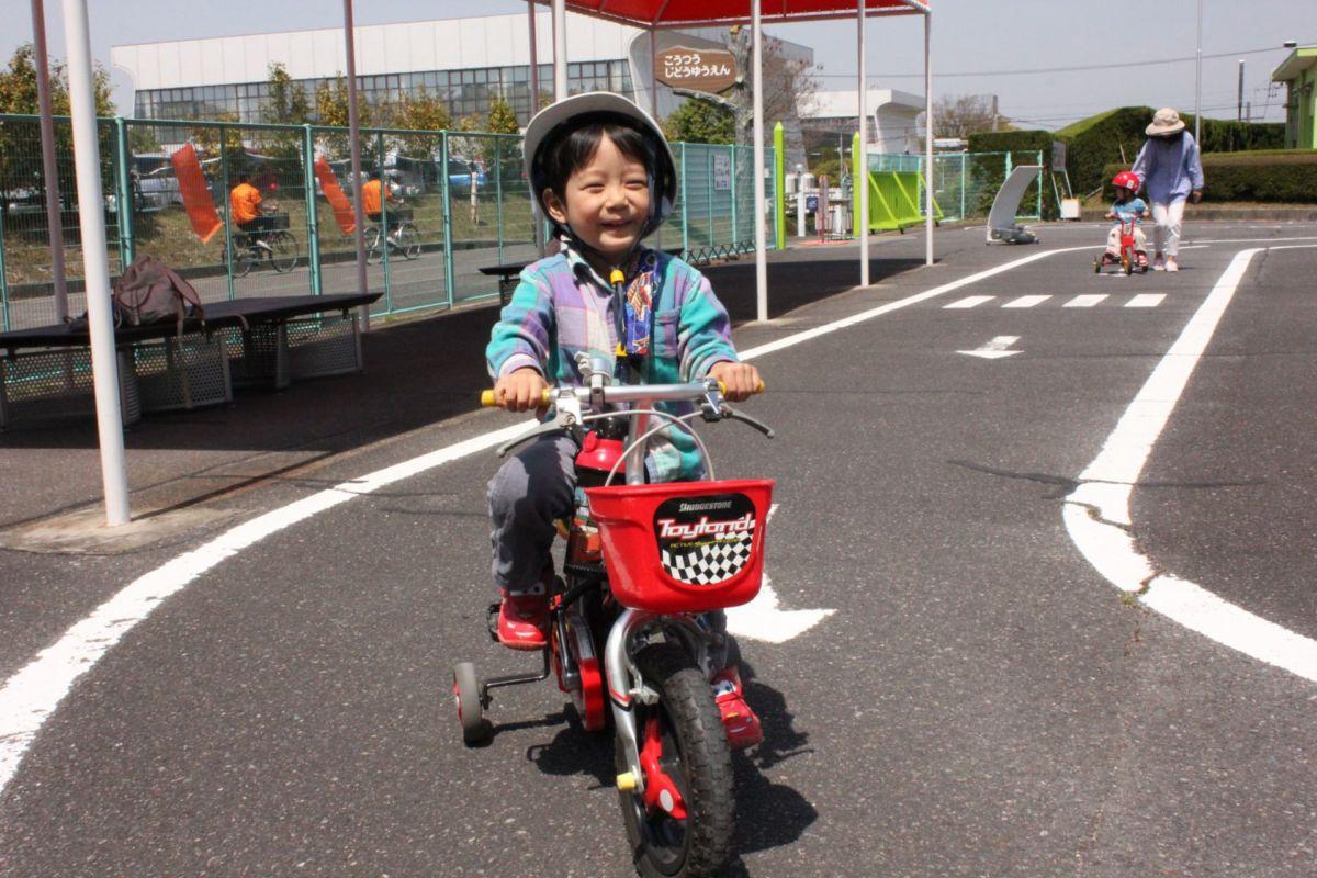 補助輪付き自転車に乗る子ども